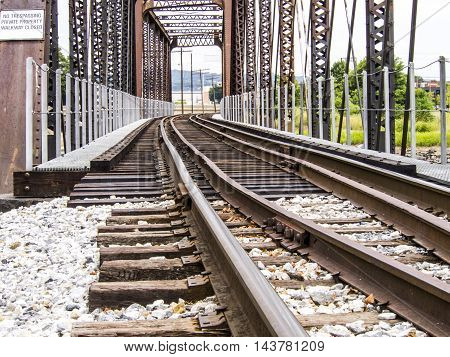 Train tracks going over a bridge that is old and rusty
