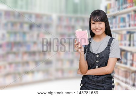 Young asian girl reading book in library