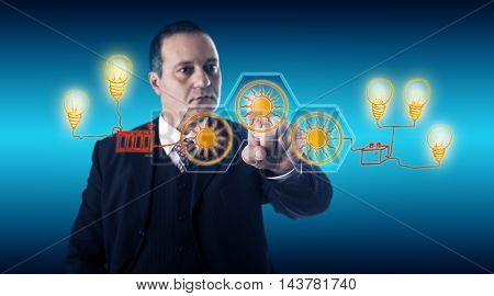 Smart businessman with focused gaze is activating solar icons for electric power generation via a touch screen. Hand-drawn storage batteries and power lines supply current to imaginary light bulbs.