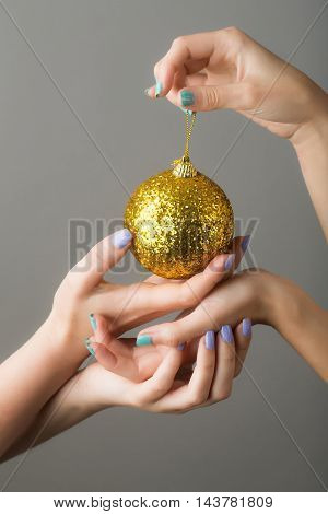 female hands with soft tender skin and blue manicure holding new year decorative ball for christmas golden color with glitter on grey background