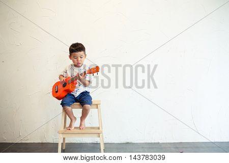 Little boy playing ukulele