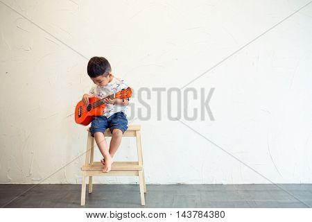 Asian Little boy playing ukulele