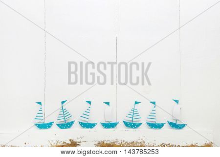 Seven blue turquoise sail boats on old shabby chic background for concepts.