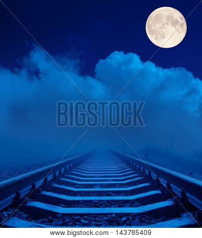railroad in night under clouds with full moon