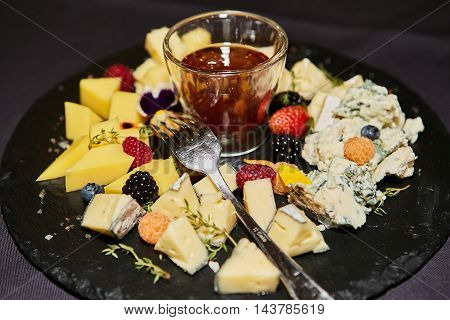 Cheese plate with berries and honey on black plate