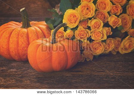 pile of orange pumpkins with yellow roses on wooden textured table, retro toned