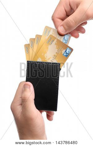 Male hand holding leather wallet with credit cards, isolated on white