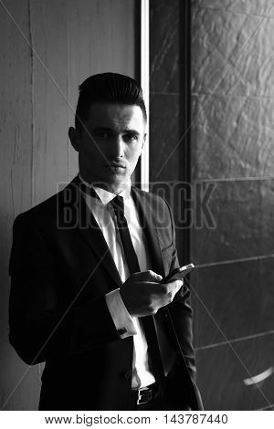 Man young handsome sensual elegant model in suit with skinny necktie with smartphone looks in camera black and white on grey background