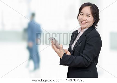 Asian businesswoman holding tablet computer and smiles