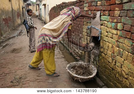 PANIPAT, HARYANA, INDIA - Aug 5 2010: A lowe caste lady practices the illegal process of manual-scavenging from a home; the removal of human waste by hand.