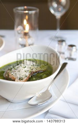 Soup at a fancy restaurant in a candlelit setting.