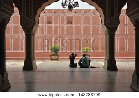 JAIPUR, RAJASTHAN, INDIA - Jul 28 2010: Visitors sit in the courtyard in Jaipur's City Palace.