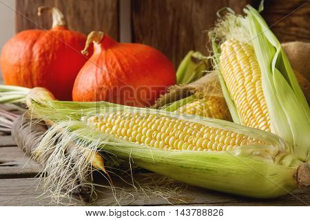 Ripe Yellow Corn And A Pumpkin Colored Carrots On Sackcloth. Woo