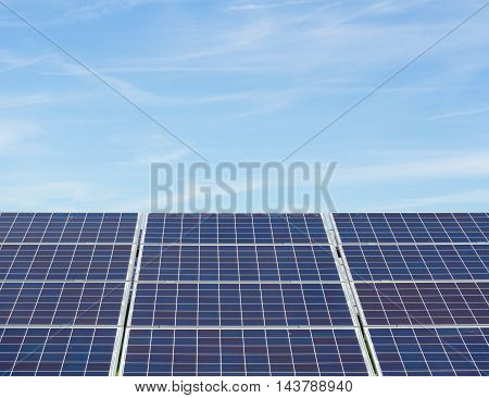 Rows of solar panels or solar cells generating clean, renewable electricity under a blue sky.