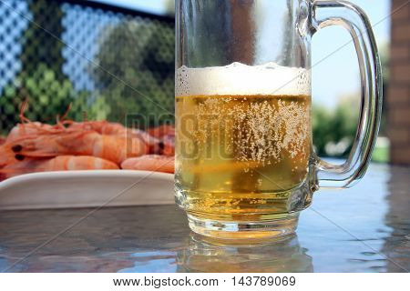 Beer mug and Fresh Organic Shrimp Cocktail at a plate