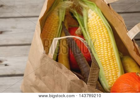 Ripe Yellow Corn And A Pumpkin Colored Carrots In A Paper Bag. A
