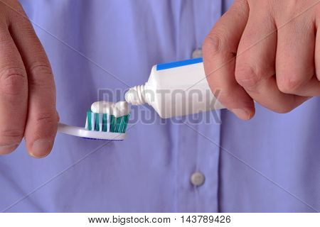 pouring toothpaste on toothbrush on white background.Toothpaste being squeezed onto toothbrush.