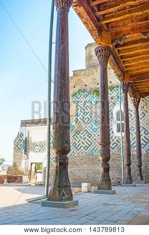 The view through the carved pillars of mosque's veranda on the ruined wall of Dorus-Saodat Mausoleum Hazrati Imam Complex Shakhrisabz Uzbekistan.