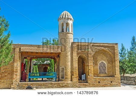 The small minaret of Mosque in Hazrat Imam Complex with the covered terrace and the trestle-bed to spend the time in shade Shakhrisabz Uzbekistan.