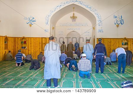 SHAKHRISABZ UZBEKISTAN - MAY 2 2015: The muslim worshipers in Hazrati Imam Mosque during the Asr prayer on May 2 in Shakhrisabz.
