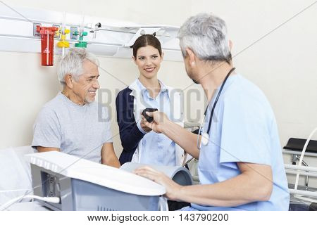 Physiotherapist Giving Belt To Colleague While Treating Senior P