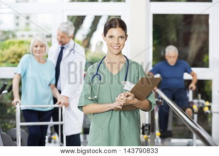 Smiling Female Physiotherapist Holding Clipboard In Fitness Cent