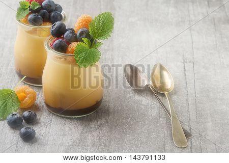 Milk Caramel Dessert In A Glass Jar With Berries, Mint. Gray Woo