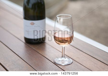 Wineglass and bottle outdoors on a table.