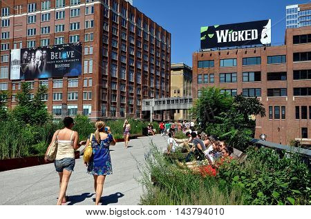 New York City - August 27 2010: People strolling reading and sunbathing on the High Line Park built atop an old elevated freight railway line on Manhattan's West Side