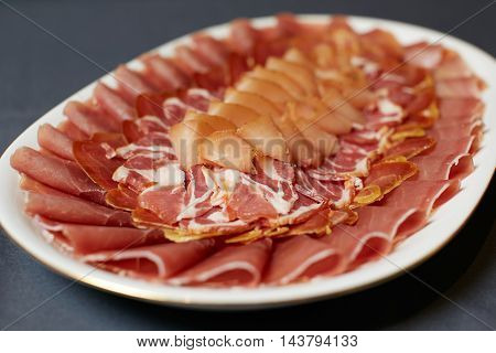 Assortment of delicatessen cold meat, salami, ham and bacon on dish. Selective focus