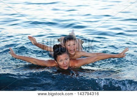 mother with son bathing in the sea having fun and laughing