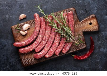 Sausages and ingredients cooking. Top view on stone table