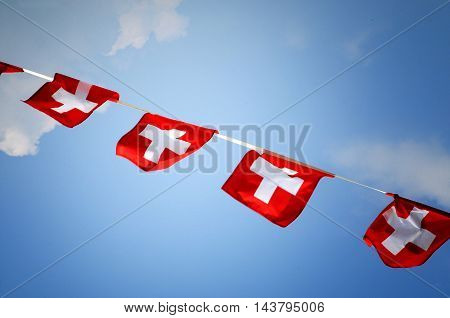 Row of colorful red bunting with the Swiss national flag flying in the breeze from a diagonal string against a blue sky for a patriotic celebration