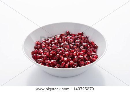 Pomegranate seeds in white ceramic bowl on white background