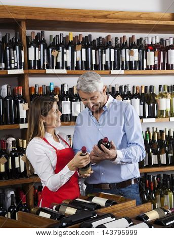 Saleswoman Showing Wine Bottles To Customer In Supermarket