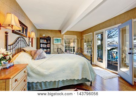 Bedroom With Hardwood Floor And Opened Door To Walkout Deck