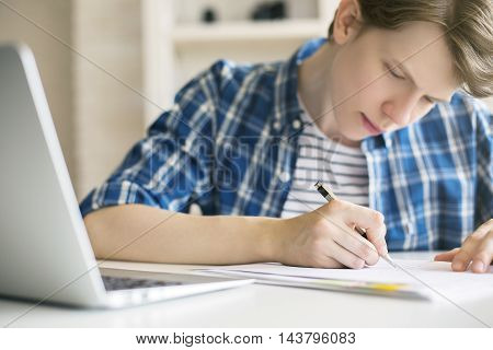 Close up of casual guy doing homework at desk with blurry laptop. White brick wall and shelves in the background