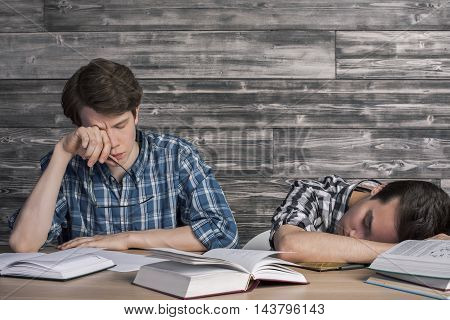 Two young college students tired of studying at wooden table with many open book. Textured wooden wall in the background