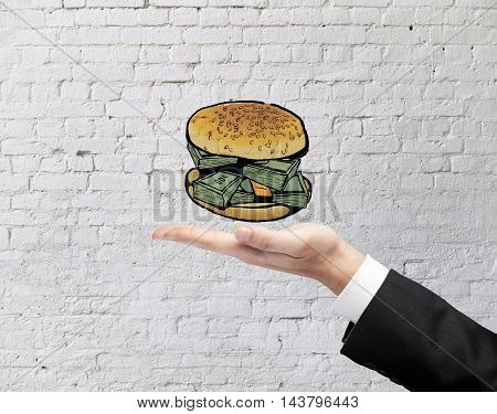 Businessman hand holding abstract dollar banknote burger on white brick wall background. Financial growth concept