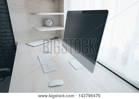 Side view of wooden workplace with blank computer screen keyboard clock and other items in black brick interior. Mock up 3D Rendering