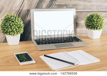 Side view of creative wooden desktop with blank white laptop smartphone notepad with pen and decorative plants. Mock up