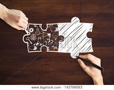 Male hands drawing puzzle pieces and success icons on wooden background. Business partnership sketch
