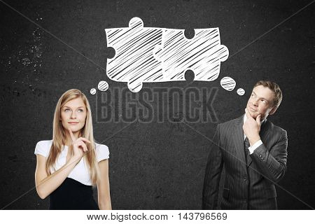 Young businessman and businesswoman thinking about puzzle pieces on concrete background. Teamwork and partnership concept