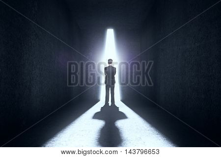 Thinking businessman standing against abstract bright light in textured concrete room. Research concept