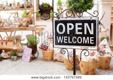 Open Welcome sign on a scrolled metal frame and pole outside a market shop selling potted plants with copy space