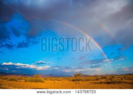 The magnificent rainbow crosses the sky over desert in Namibia. Dirt road in the African steppe. The concept of exotic tourism