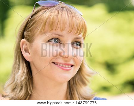 Close up of attractive young woman outside in summer nature. Portrait of beautiful charming smiling female. Perfect girl with eyeglasses thinking and looking sideways in a park.