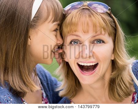 Smiling mother and daughter whispering gossip - relationships and happiness concept. A little girl telling her mother a secret. Portrait of happy family - sharing secrets, outdoors at park.
