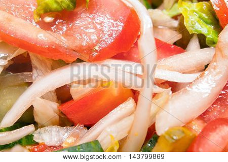 Salad with fresh tomatoes cucumbers and onion filled with olive oil close up