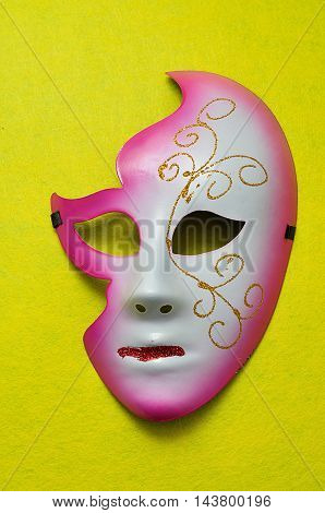 A carnival mask displayed on a yellow background